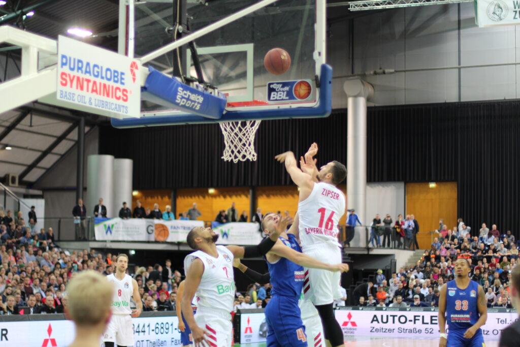 Nahaufnahme einer Spielszene aus dem Basketball-Bundesligaspiel SYNTAININCS MBC gegen FC Bayern München. Paul Zipser springt unter dem Korb am höchsten in Richtung eines in der Luft fliegenden Balles. Im Hintergrund sind zahlreiche Zuschauer zu sehen, Foto: Anneke Elsner.
