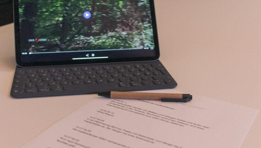Der Osten: Auf einem Tisch liegt ein computerbedrucktes Blatt Papier, darauf ein Stift. Daneben steht ein Tablet auf dem ein Video abgespielt wird, Foto: Florian Eib.