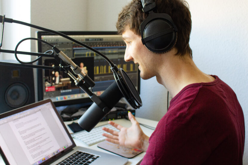Sprecher Florian Eib sitzt an einem Schreibtisch vor einem Mikrofon. Er blickt auf einen Laptop auf dem ein Text abläuft. Im Hintergrund ein Monitor auf dem ein Aufnahmeprogramm abläuft. Kultur in Zeiten von Corona per Livestream oder barrierefreiem Video, Foto: Tomke Koop.