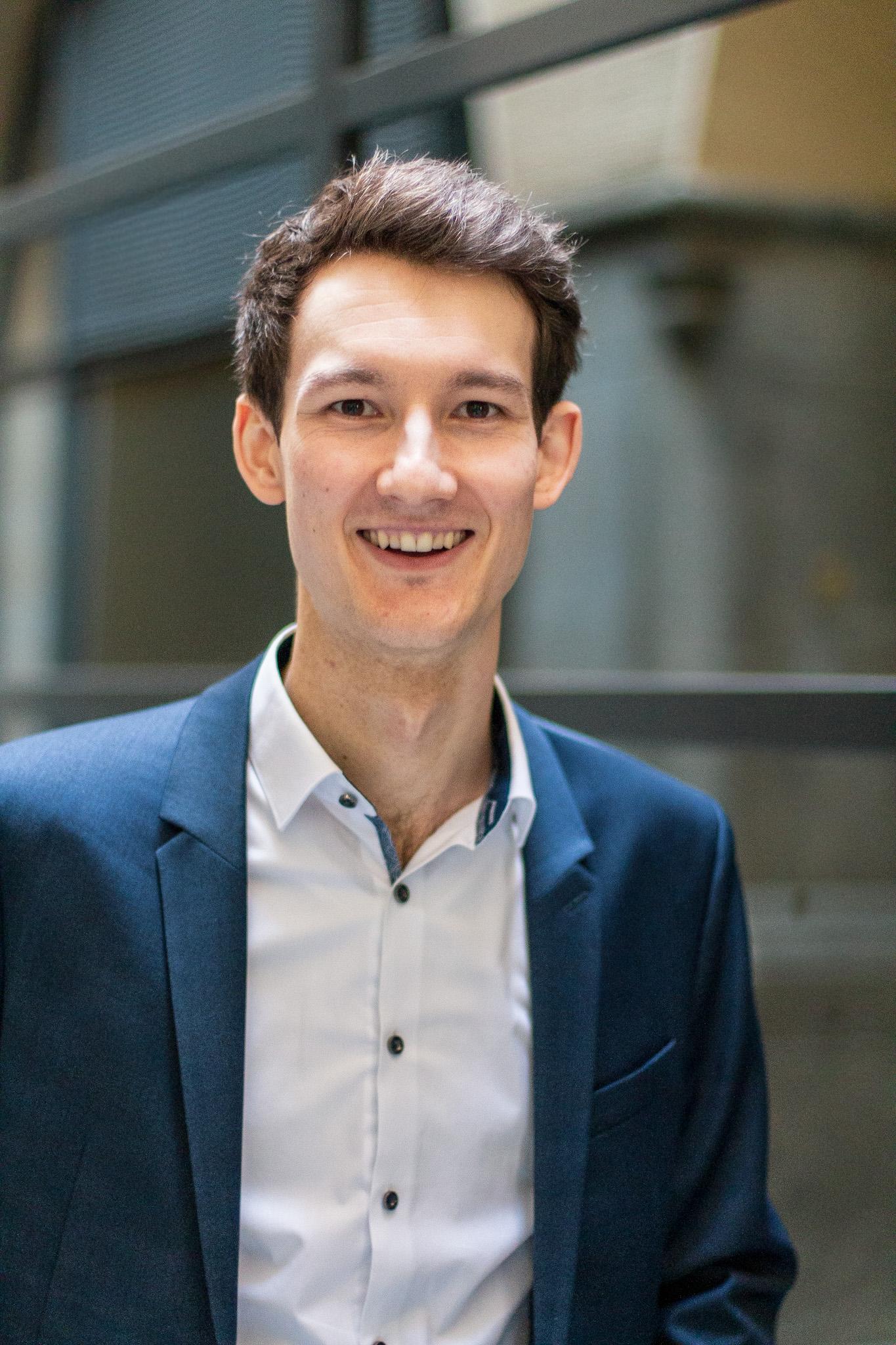 Kontakt Florian Eib: Der Sportreporter in Sack und weißem Hemd blickt lächelnd in die Kamera, Foto: Tomke Koop.