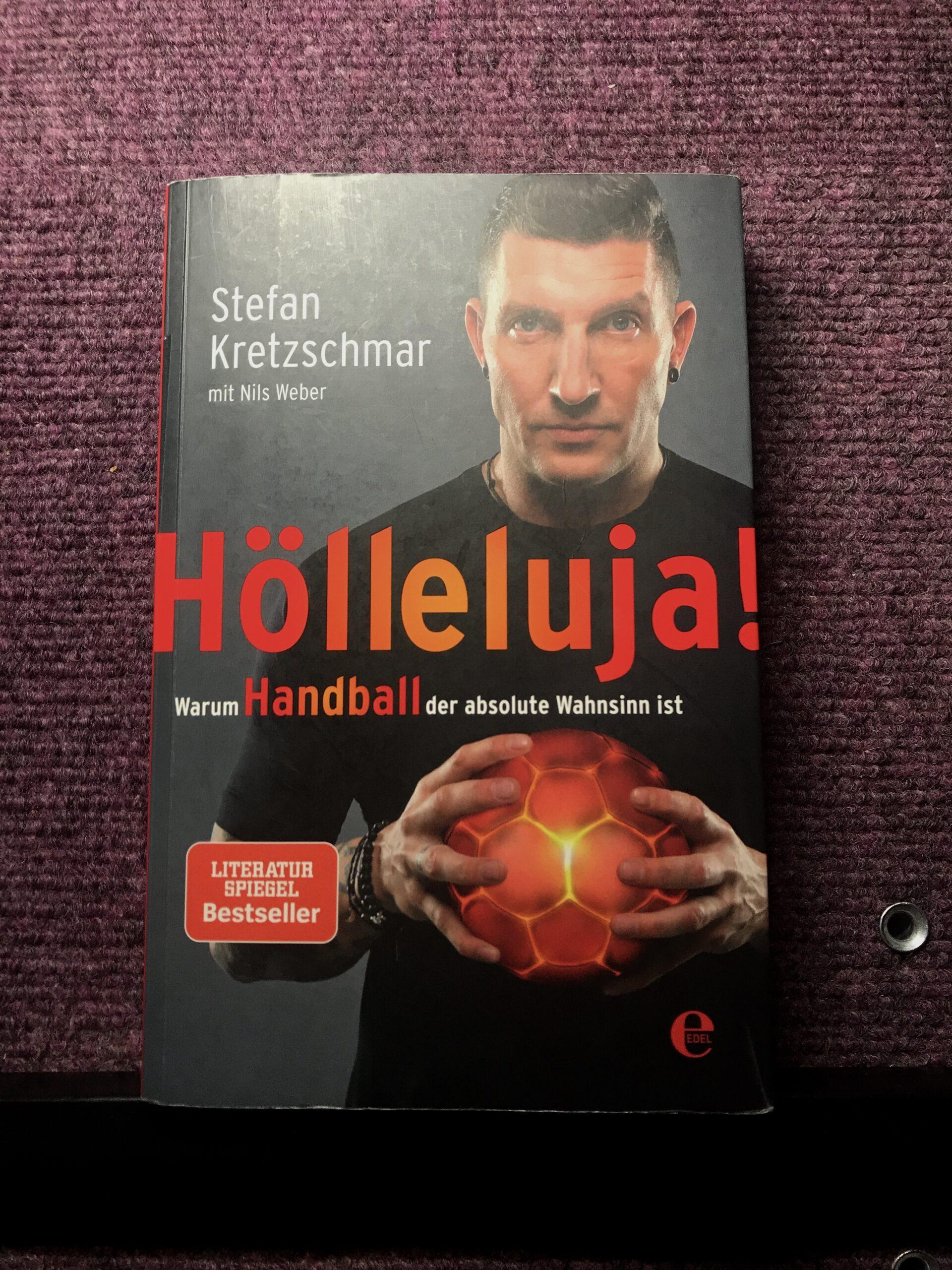 """Coverbild des Spielgel-Bestseller """"Hölleluja. Warum Handball der absolute Wahnsinn ist"""". Stefan Kretzschmar mit dunklen kurzen Haaren und in einem schwarzen T-Shirt, blickt in die Kamera. Mit beiden Händen packt der einen Handball. Der Handball ist glutrot eingefärbt, Foto: Florian Eib."""