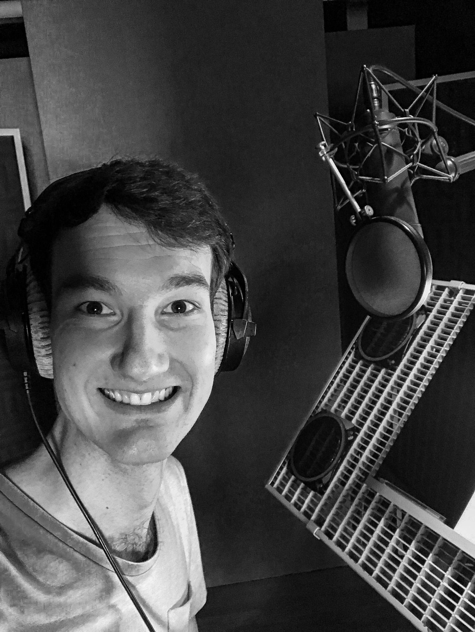 Ein Schwarz-Weiß-Selfie von Werbesprecher Florian Eib. Er grinst in die Kamera und hat einen Studiokopfhörer auf. Rechts im Bild befindet sich ein großes Aufnahmemikrofon mit einem Popschutz davor. Das Mikrofon hängt über einer Textablage, Foto: Florian Eib.