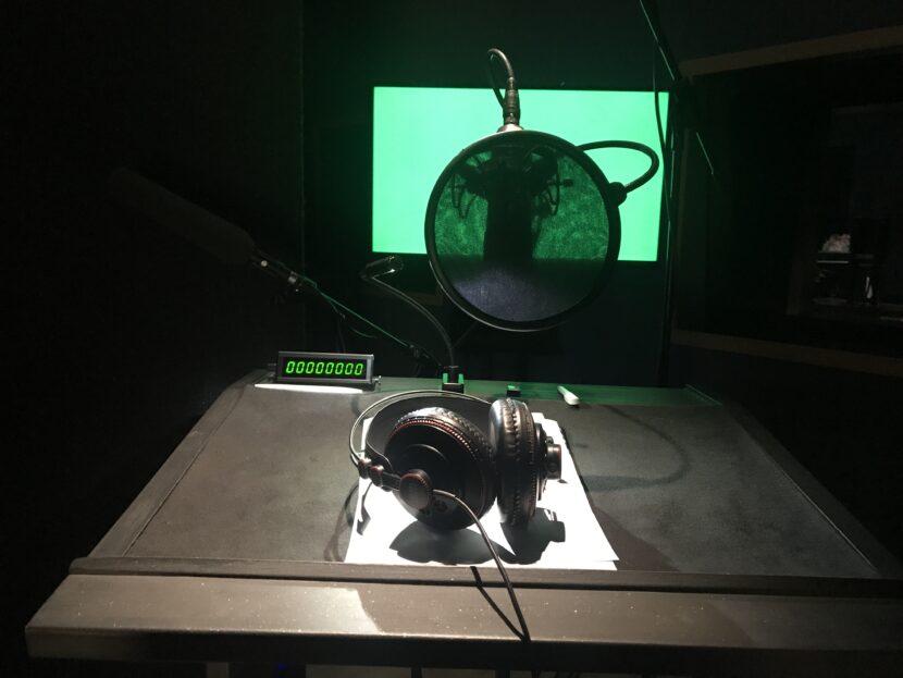 Eine Fotografie zeigt Kopfhörer auf einem schwarzen Tisch vor einem Mikrofon mit Pop-Schutz. Im Hintergrund ist ein Bildschirm mit grünem Bild. So oder so ähnlich sieht der Arbeitsplatz für Sprecher Florian Eib bei Produktionen mit Audiodeskription aus, Foto: Florian Eib